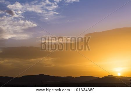 The sun descending over mountains. Blue sky and peaceful atmosphere.