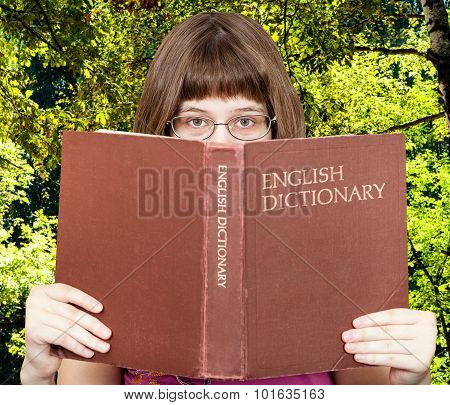 Girl Looks Over English Dictionary And Green Woods