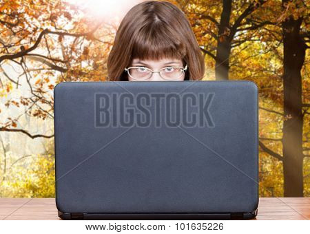 Girl Looks Over Cover Of Laptop In Autumn Woods