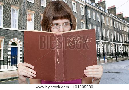 Girl Reads Over English Dictionary And House