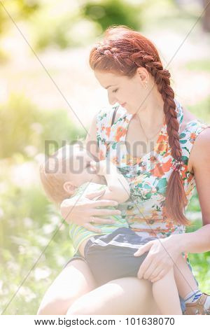 Beautiful Happy Mother Breastfeeding Outdoor