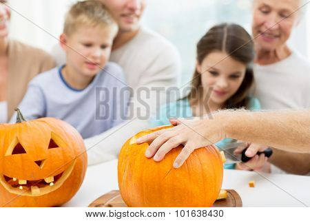 family, helloween, generation, holidays and people concept - happy family making jack-o-lantern of pumpkins at home