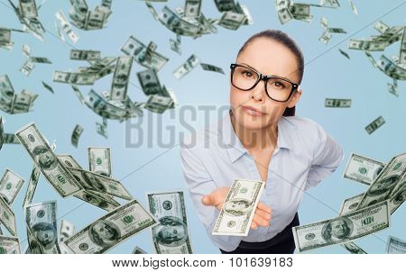business, money, financial crisis and banking concept - displeased businesswoman in eyeglasses with dollar cash money over blue background