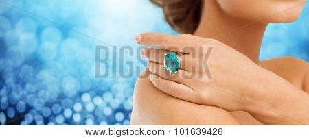 people, jewelry, luxury and glamour concept - close up of woman hand and ring with precious gem over blue lights background