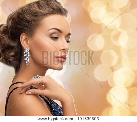 people, holidays and glamour concept - beautiful woman in evening dress wearing ring and earrings over beige lights background