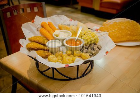 Mixed platter beautifully arranged with mix of typical latin foods such as empanadas, corn, abbas an