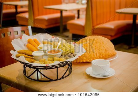 Mixed platter beautifully arranged with mix of typical latin foods such as empanadas, corn, abbas, s