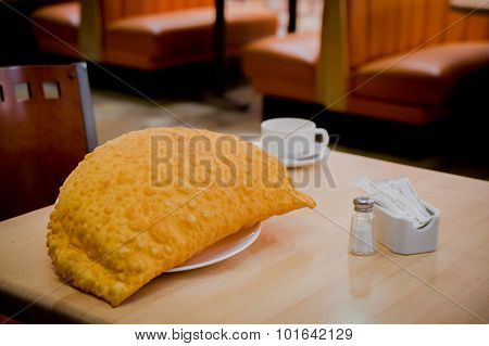 Large empanada and white coffee cup sitting on restaurant table with salt pepper visible