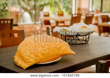 Large empanada on wooden table next to basket of typical latin foods, refreshing restaurant setting