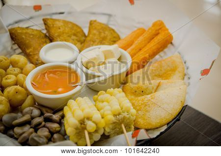 Closeup delicious food platter of typical latin foods such as corn, empanadas, abbas, cheese and sal