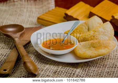 Three empanadas nicely arranged on white platter next to small salsa bowl and rustic background