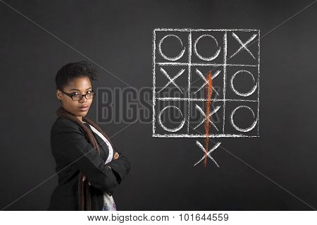 South African Or African American Woman Teacher Or Student With Arms Folded Tic Tac Toe Diagram On C