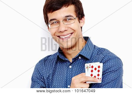 Close up portrait of young hispanic man wearing blue shirt and glasses holding Jack Ten in his hand and smiling against white wall - gambling concept