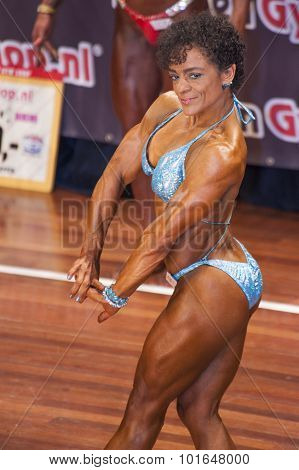 Female Bodybuilder In Chest Pose With Blue Bikini