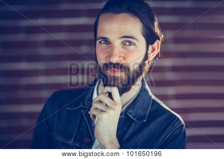 Portrait of smiling man with hand on chin against wall