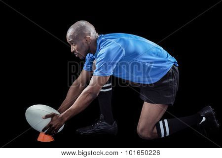 Rugby player keeping ball on kicking tee against black background