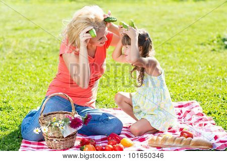 Mother and child having fun picnicking on grass