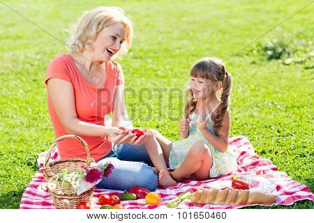 family mom and kid picnicking on lawn with vegetables