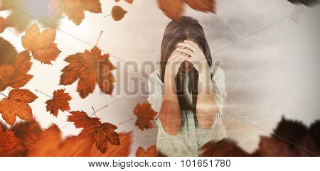 Troubled woman crying against autumn leaves