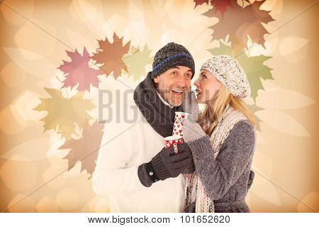 Happy couple gossiping while drinking hot tea against autumnal leaf pattern in warm tones