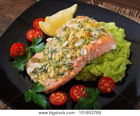 Baked salmon with cheese and almond crust and garnished with mashed potatoes and green peas