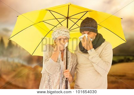 Couple sneezing in tissue while standing under umbrella against country scene