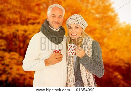 Portrait of happy couple drinking hot coffee against autumn scene
