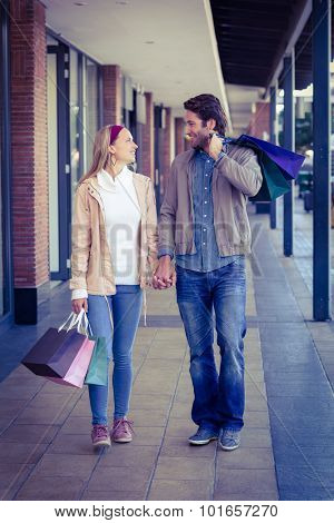 Smiling couple walking hand in hand with shopping bags at shopping mall