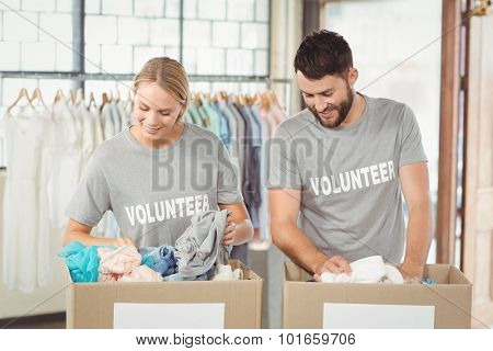 Volunteers separating donations clothes in office