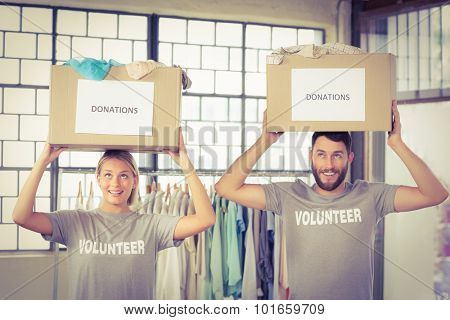 Volunteers carrying donation boxes on head in office