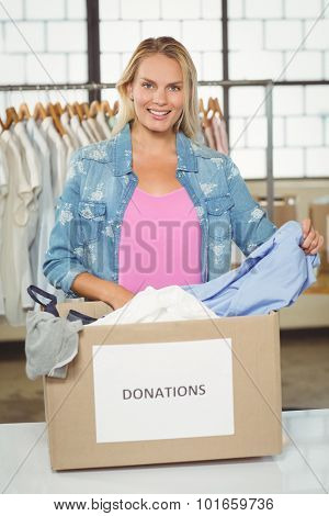 Portrait of woman separating clothes from donation box while standing in office