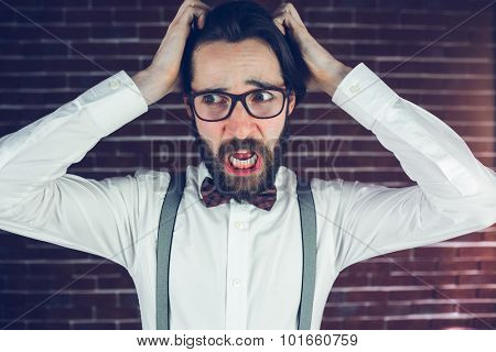 Worried man with head in hands looking away against brick wall