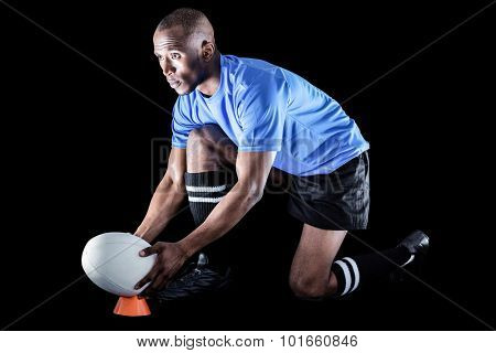 Rugby player looking away while keeping ball on kicking tee on black background