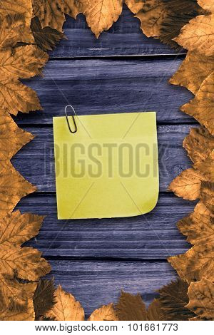 Sticky note with grey paperclip against autumn leaves on wood