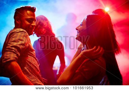 Happy young couple dancing at party in disco club