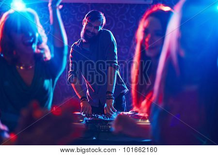 Happy bearded deejay standing by turntables in front of dancing crowd and looking at camera