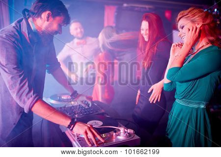Glamorous girls dancing by dj adjusting sound on turntables in night club