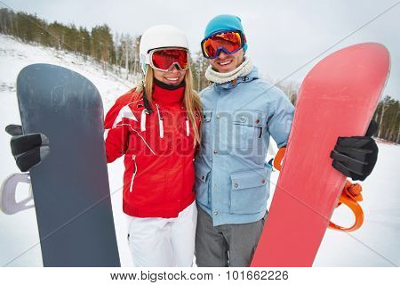 Contemporary snowboarders in winter activewear and goggles looking at camera on resort