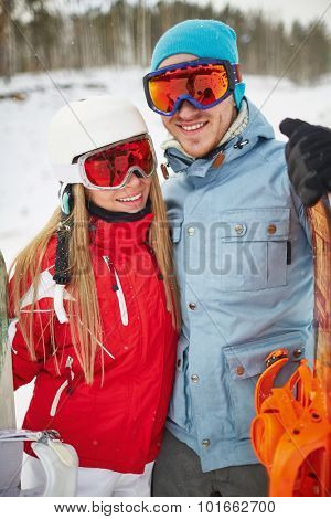 Couple of happy snowboarders in winter activewear looking at camera on resort
