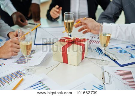 Hands of colleagues discussing papers on Christmas eve at workplace with champagne and giftbox