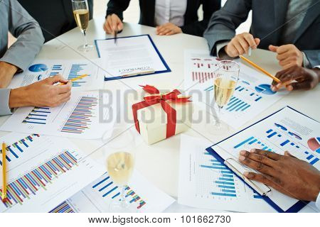 Group of employees analyzing marketing data on Christmas eve at workplace with champagne and giftbox