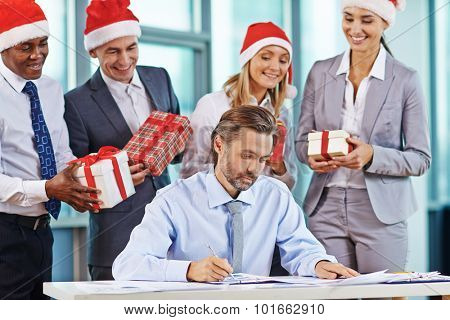 Serious businessman working with papers with his partners holding giftboxes behind