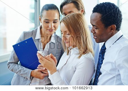 Businesswoman with cellphone and her colleagues reading sms