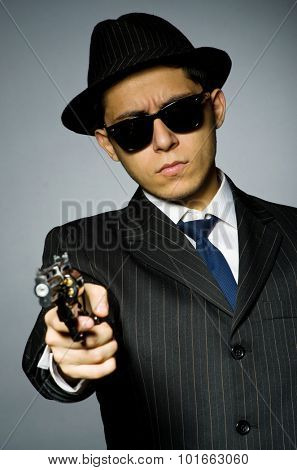 Young man in elegant suit holding handgun against gray