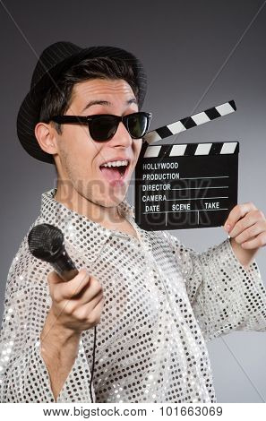 Young cheerful man with clapperboard and microphone