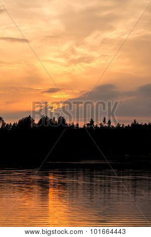Fiery sunset at lakeside and silhouette forest
