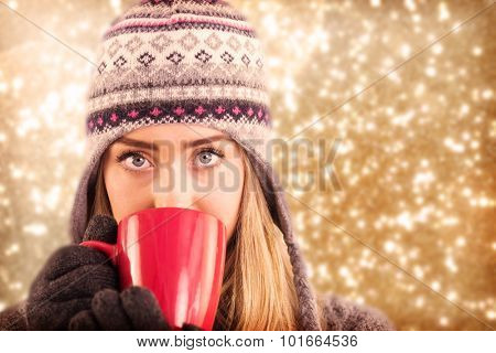 Happy blonde in winter clothes holding mug against white snow and stars design