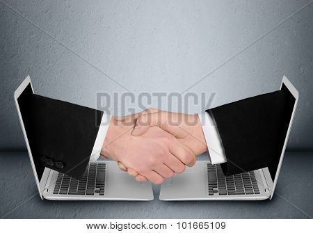 Business people handshake through computer