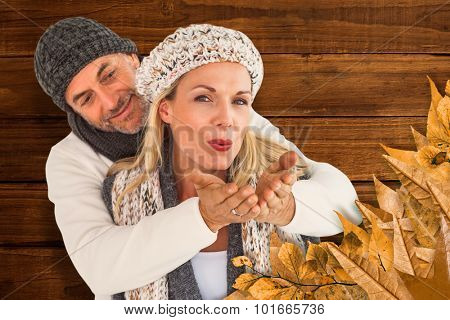 Husband hugging wife from behind as she blows kiss in air against overhead of wooden planks