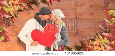 Couple holding heart while looking at each other against bleached wooden planks background